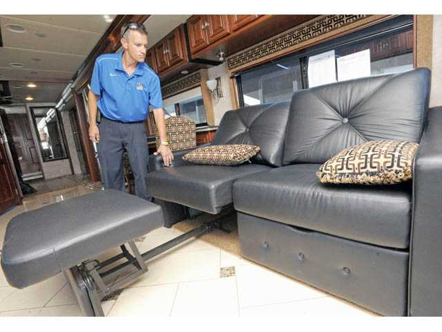 Beau Brixey demonstrates a sectional sofa, extendable as a bed, in a 2012 Itasca Ellipse motor home.