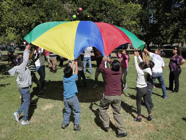 In this photo taken Thursday, children and adults uses a play parachute as past of an exercise activity during a wellness program run jointly by the La Familia Counseling Center INC., and the YMCA in Sacramento.