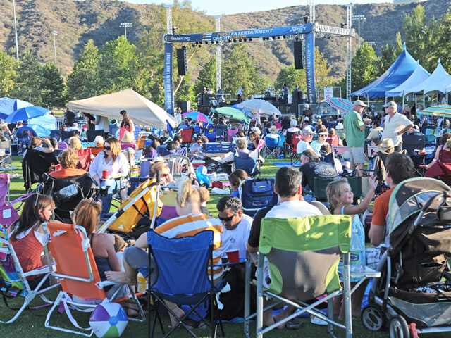 Audience members relax on the lawn at Central Park in Saugus during Concerts in the Park.