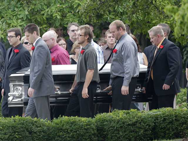 Pallbearers carry Matt McQuinn, killed in the Aurora, Colorado movie theater shooting, from the church after his funeral Saturday, in Springfield, Ohio.