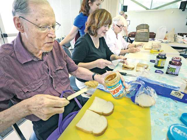 Blair Uhl, left, spreads peanut butter on bread as he joins volunteers in the lounge of St. Stephen's Episcopal Church in Santa Clarita on Thursday.