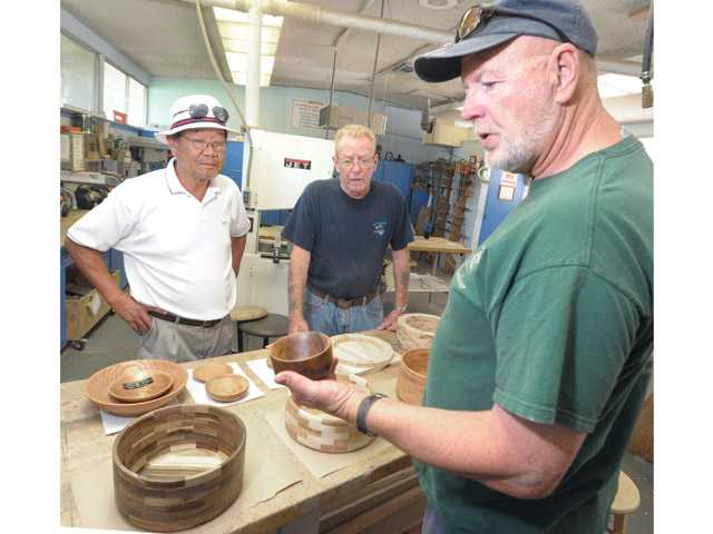 Gary Simpson, right, shows a finished bowl with John Lamkin, center, and Yoshi Muramatsu, right, in the Friendly Valley wood shop on Thursday.