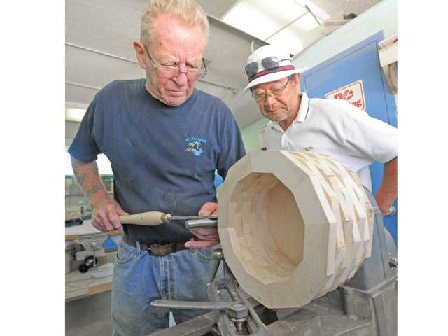 John Lamkin, left, and Yoshi Muramatsu set up the wood lathe before starting the process of using a wood chisel to shape a laminated hardwood bowl blank on the lathe with in the Friendly Valley wood shop on Thursday.
