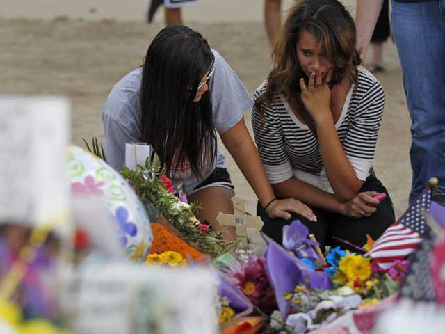 Brittani Roehr, left, from Wichita, Kan., and Chelsea Holi, from Aurora, react at the memorial across from the movie theater, Sunday in Aurora, Colo.