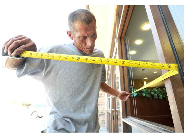 Dan Orchard of Preferred Glass & Windows takes measurements in a window frame at the Bank of Santa Clarita's branch in Canyon Country on Monday.
