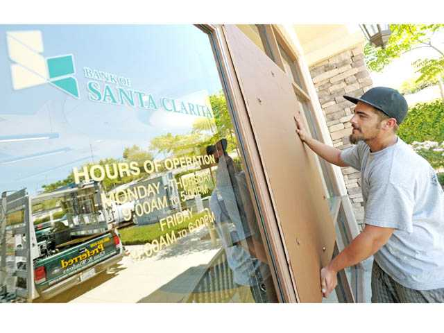 Trent Kennon of Preferred Glass & Windows boards up a window Monday that was shattered by a tire after an early-Sunday morning solo SUV crash near the Bank of Santa Clarita's Canyon Country branch.