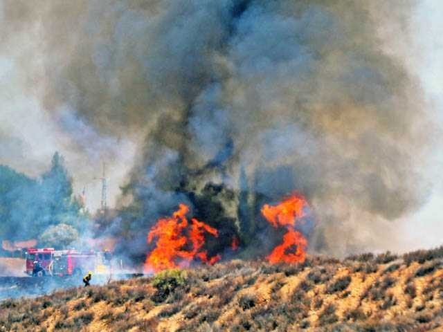 Flames burn brush in the hills above Lake Hughes Road as seen from the intersection with Ridge Route Road in Castaic on Monday.