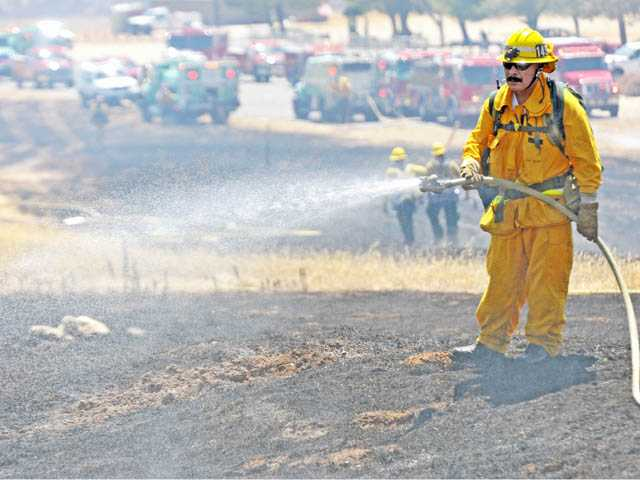 A firefighter from Fire Station 149 works in the mop-up operation after crews contain a brush fire off Lake Hughes Road in Castaic on Monday.
