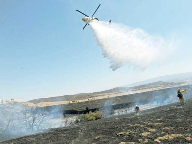 A fire helicopter drops water over brush charred by a fire off Lake Hughes Road in Castaic on Monday.