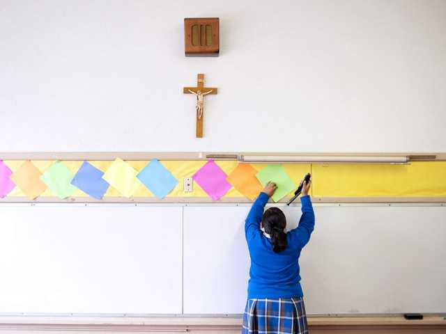 This July 18 photo shows Adriana Landeros stapling colored paper to the wall of a classroom after summer school at Our Lady of Lourdes in Los Angeles.