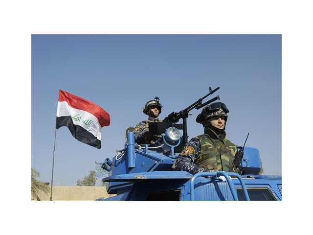 The Iraqi flag waves while federal police parade in Baghdad.