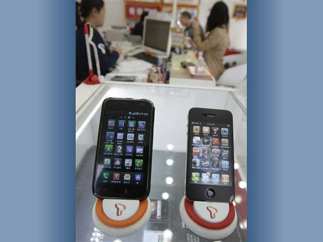 Samsung Electronics' Galaxy S, left, and Apple's iPhone 4 are displayed at a mobile phone shop in Seoul, South Korea.