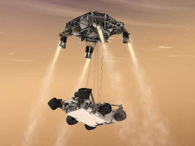 "In this 2011 file artist's rendering provided by NASA/JPL-Caltech, a ""sky crane"" lowers the Mars Science Laboratory Curiosity rover onto the surface of Mars."
