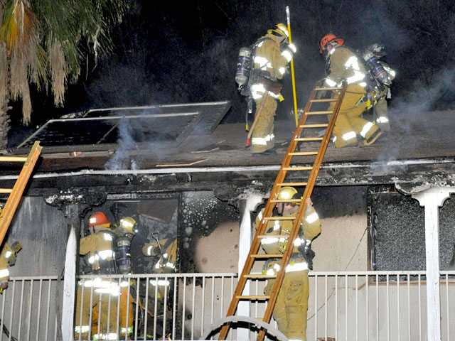 Firefighters control a fire in a two-story home on the 26300 block of Larkhaven Place in Canyon Country late Monday night.
