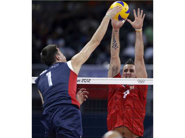United States player Matthew Anderson, left, spikes the ball over Germany's Gyorgy Grozer during a men's preliminary volleyball on Tuesday in London.