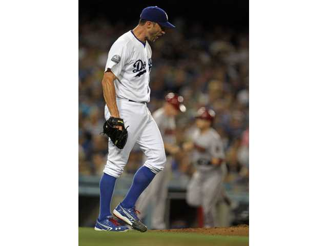 Los Angeles Dodgers starting pitcher Chris Capuano walks back to the mound after giving up a three-run home run on Tuesday in Los Angeles.