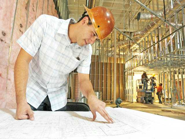 Project manager Daniel Sepulveda, of Sepulveda Commercial Development, looks over blueprints on July 23 as a crew works on the interior of the future LA Fitness club in Stevenson Ranch.