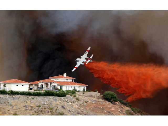 A firefighting air tanker drops fire retardant on a hillside as a wildfire rages on Wednesday in Murrieta. Several homes were threatened by the wildfire that burned more than 200 acres.