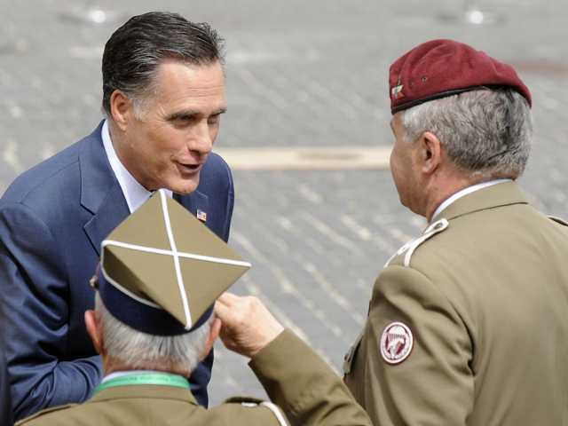 U.S. Republican presidential candidate, former Massachusetts Gov. Mitt Romney speaks with Polish WWII veterans after laying a wreath at the Warsaw 1944 Uprising monument in Warsaw, Poland, on Tuesday.