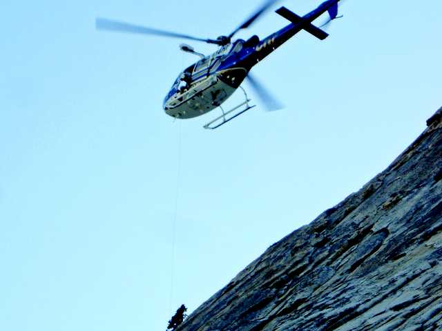 A helicopter and Fresno County Sheriff's search and rescue team member rescue a Santa Barbara, Calif. man from a rocky ledge on Dog Tooth Peak in the Sierra Nevada, 45 miles northeast of Fresno, Calif. A hiker weary from clinging to the side of a Sierra peak for days was rescued by a sheriff's deputy who sprinted 300 feet up the 45-degree slope just as the hiker was losing his grip.