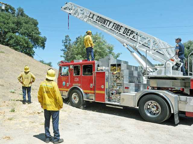 Los Angeles County Fire Department's Quint 126 is stationed at the scene where a man hanged himself from a utility pole in Newhall Avenue in Newhall on Saturday.