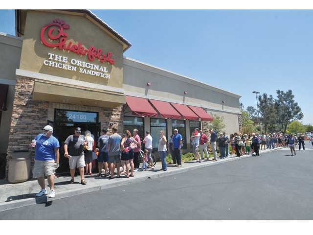 Hundreds line up outside of Chick-fil-A restaurant with dozens of cars in the drive-thru line at the Westfield Valencia Town Center Mall in Valencia for Chick-fil-A Appreciation Day on Wednesday.