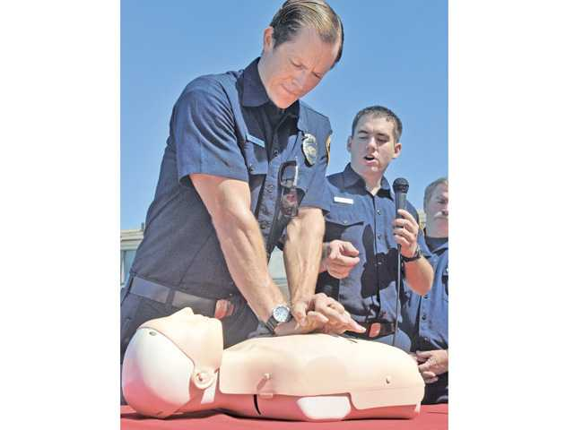 L.A. County firefighter/paramedics Nate Denver, left, and Andrew Herrera demonstrate life saving chest compression t echnique as it might be used on a drowning victim at a city of Santa Clarita press conference at North Oaks Park Pool in Canyon Country to raise pool safety awareness on Wednesday.