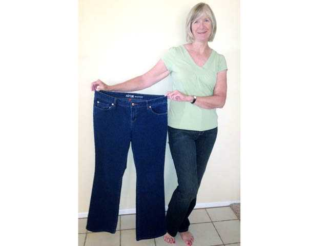 "Jan Broneer displays her ""before"" jeans. She joined Results Fitness four years ago at age 58."