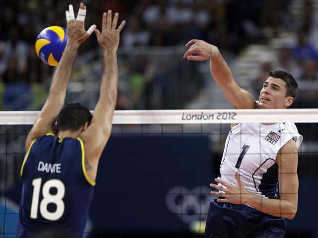 The United States' Matthew Anderson, right, spikes the ball past Brazil's Dante Amaral during a men's preliminary volleyball match at the 2012 Summer Olympics on Thursday in London.