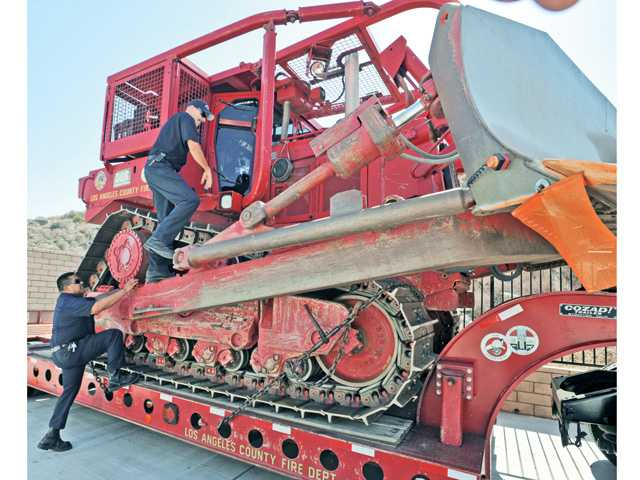 Wright and Valerio, part of the three-man crew climb into the $1.1 million, 95,000-pound tractor.