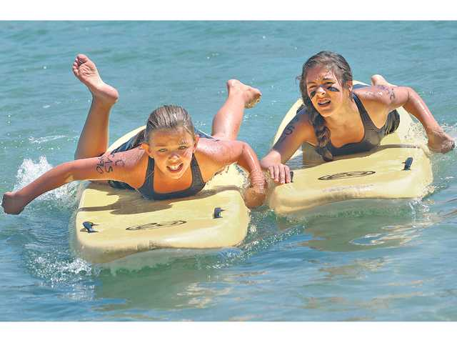 Castaic Junior lifeguards Taylor Robars, 11, left, and Jillian Abreu, 11, fight for position as they near the beach during the 200 meter paddle relay competition at Castaic Lake in Castaic on Thursday.