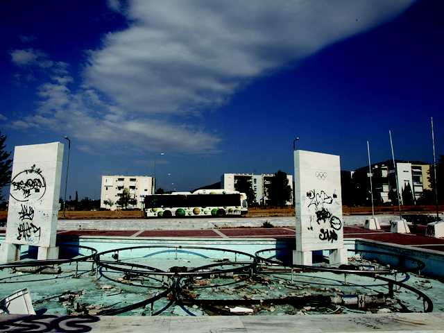 A bus passes the remains of a fountain made with Olympic rings and graffiti-defaced marble blocks that were originally dedicated to Greek Olympic medal winners, at the former Olympic village on the northern fringes of Athens, Thursday. After the Athens 2004 Games, the village was used as a worker housing project.