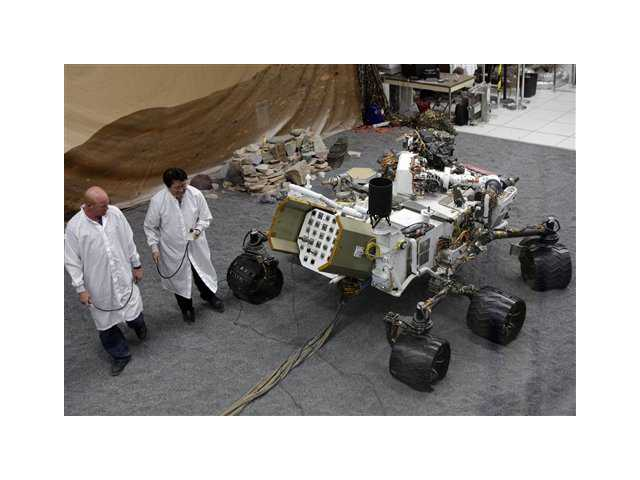 Engineers work on a model of the Mars rover Curiosity at the Spacecraft Assembly Facility at NASA's Jet Propulsion Laboratory in Pasadena.