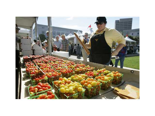 Benina Burroughs of Merced, Calif., looks over a display of cherry tomatoes by Farmers with ALBA from Salinas, Calif., at a farmer's market during Slow Food Nation in San Francisco.
