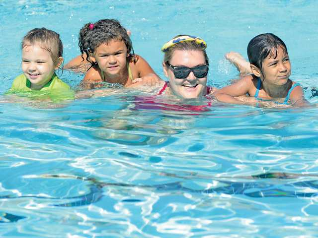 Santa Clarita Lifeguard Loretta Rowley, second right, works with children during a swim class at North Oaks Park Pool in Canyon Country before a press conference on pool safety awareness on Wednesday.