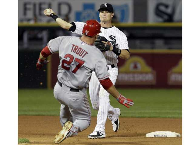 Chicago White Sox second baseman Gordon Beckham, right, throws to first after forcing out LosAngelesAngels' Mike Trout during the fourth inning of a baseball game in Chicago on Friday.