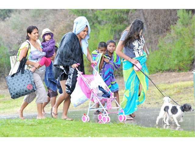 The Perez family, of Palmdale, retreat from inclement weather to their car at the Castaic Lake Recreation Area on Friday.