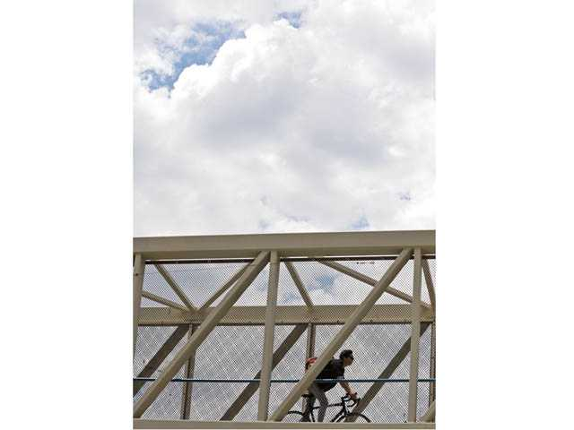 A cyclist rides through a paseo over Valencia Boulevard in Valencia as clouds loom overhead on Friday.