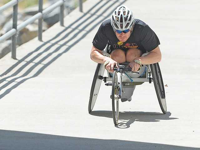 Valencia High graduate Kevin Mather was left paralyzed after being struck by a truck in 2009. The 29-year-old, though, has earned a spot in the Oct. 13 Ironman World Championship.