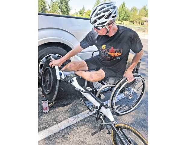 Valencia High graduate Kevin Mather transitions from his wheelchair to his racing chair as he prepares to train on Wednesday.