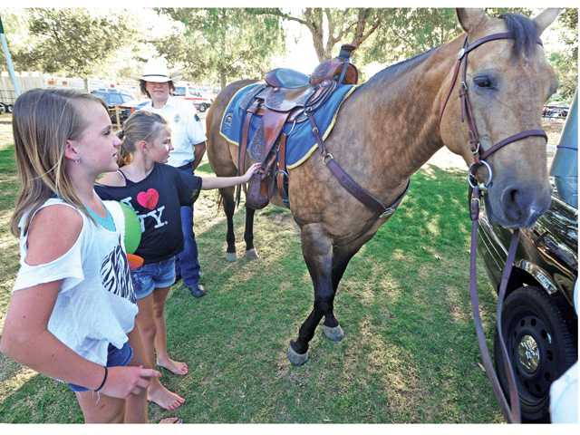 Macy Hernandez, 11, left, and Brianna Peoples, 10, of Valencia, pet Amber of the Los Angeles County Sheriff's Department's SCV Mounted Posse at the National Night Out.
