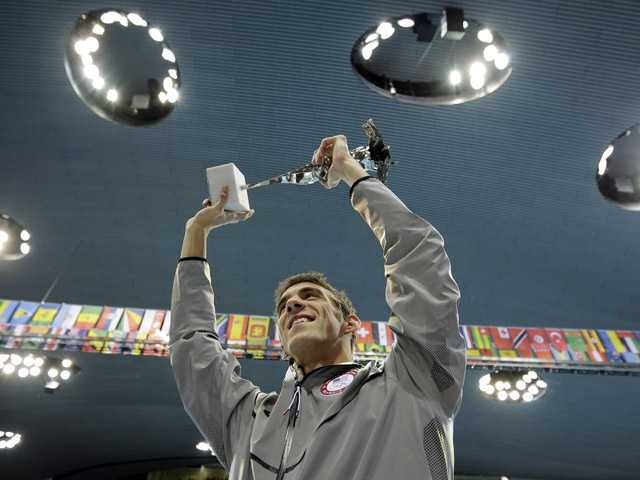 United States swimmer Michael Phelps holds up a silver trophy after being honored as the most decorated Olympian at the Aquatics Centre in the Olympic Park during the 2012 Summer Olympics in London on Saturday. Phelps was honored with a special individual ceremony after concluding his record-breaking career Saturday as the most decorated Olympian. Phelps pushed the United States in front to win the medley relay Saturday in the final swimming event of the London Games, after which he is retiring.