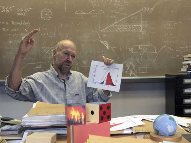 Dr. James E. Hansen head of the NASA Goddard Institute for Space Studies gestures during an interview about weather extremes on Thursday with the Associated Press at his office in New York.