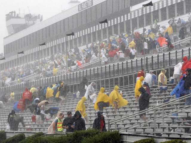 Fans leave the stands after the start of the NASCAR Sprint Cup Series auto race was postponed due to rain on Sunday at Pocono Raceway in Long Pond, Pa.