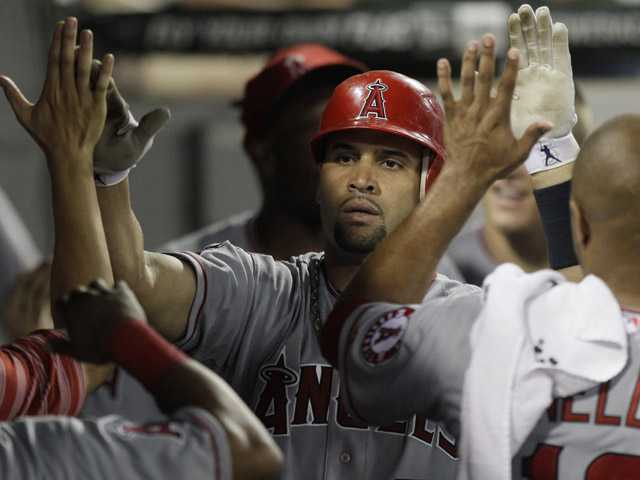 Los Angeles Angel Albert Pujols celebrates with teammates after hitting a solo home run during the seventh inning against the Chicago White Sox in Chicago on Saturday.