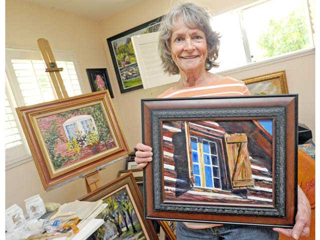 "Jane Dietz works on a painting of an ""early"" summer cabin in Mammoth in the studio of her Newhall home on Thursday."