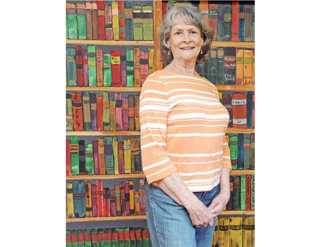 "Dietz in front of a ""library"" she painted in a room of her home. Dietz paints in book titles and authors based on personal experiences of family members and guests."