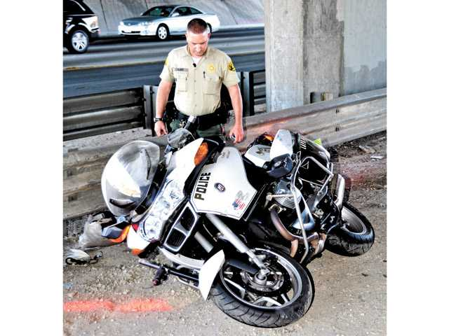 An SCV Sheriff's Station deputy examines an LAPD motorcycle on southbound Interstate 5 near Lyons Avenue on Sunday.