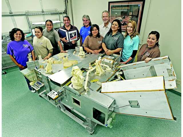 Tri-Tek Electronics employees posed in this photo from June 5, 2011, next to the mock up of JPL's Mars rover Curiosity. The team built the electronic harnesses for the unit.