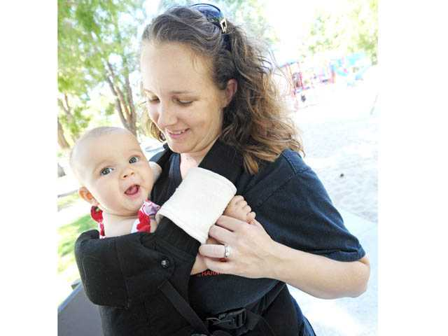 Terri Kurcab, of Canyon Country, spends a moment with her daughter Alexandria, 5 months, in a baby carrier at Bouquet Canyon Park in Saugus on Tuesday.